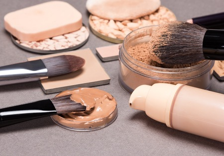 Makeup products to even out skin tone and complexion on brown textured surface