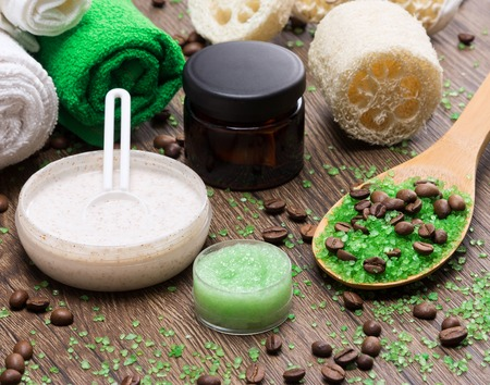 busting: Anti-cellulite cosmetics with caffeine. Wooden spoon with green coarse sea salt and coffee beans, natural body scrubs, skin care creams, body scrubbers, towels. Spa and cellulite busting products