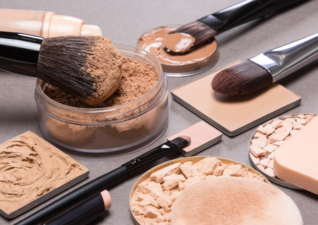 even: Makeup products and accessories to even out skin tone and complexion: loose and compact powders, concealer pencil, correctors, liquid foundation with brushes and cosmetic sponges on textured surface