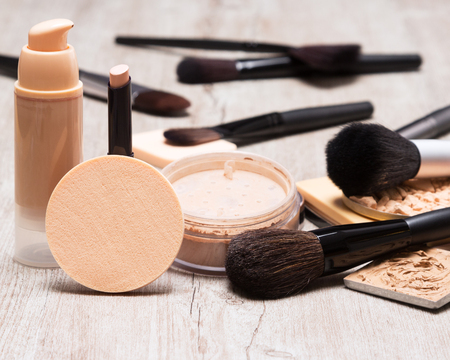 Makeup products and accessories to even out skin tone and complexion. Round cosmetic sponge, bottle of liquid foundation, concealer pencil, jar of loose powder, makeup brushes on shabby wooden surface