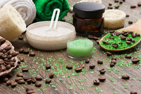 busting: Anti-cellulite cosmetics with caffeine. Wooden spoon with sea salt and coffee beans, natural body scrubs, skin care cream, towels, loofah. Spa and cellulite busting products. Shallow depth of field