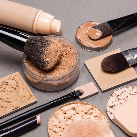 Makeup products and accessories to even out skin tone and complexion: loose and compact powders, concealer pencil, correctors, liquid foundation with brushes and cosmetic sponges on textured surface