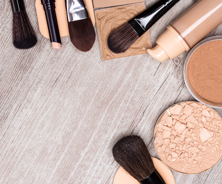 Makeup products and accessories to even out skin tone and complexion laid out as frame on shabby wooden surface. Concealer pencil, foundation, powders, cosmetic sponges, makeup brushes. Copy space