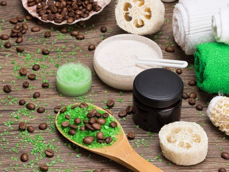 Anti-cellulite cosmetics with caffeine. Wooden spoon with green coarse sea salt and coffee beans, natural body scrubs, skin care cream, body scrubbers, towels. Spa and cellulite busting products Фото со стока - 53297565