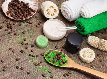 busting: Anti-cellulite cosmetics with caffeine. Wooden spoon with green coarse sea salt and coffee beans, natural body scrubs, skin care cream, body scrubbers, towels. Spa and cellulite busting products Stock Photo