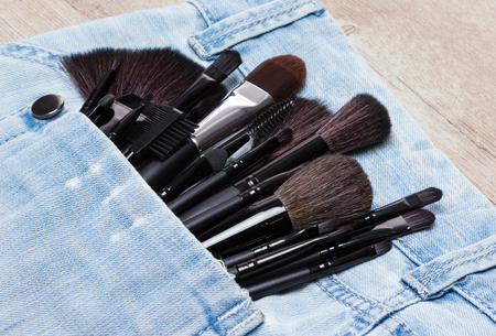 eyebrow trimming: Professional tools of make-up artist in shabby jeans pocket. Sponge tip applicators and makeup brushes: for applying foundation, powder, blush, eyeshadow, eyebrow brushes and others. Selective focus Stock Photo