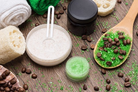 scrubbers: Anti-cellulite cosmetics with caffeine. Wooden spoon with green coarse sea salt and coffee beans, natural body scrubs, skin care cream, body scrubbers, towels. Spa and cellulite busting products Stock Photo