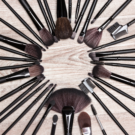 eyebrow trimming: Various makeup brushes laid out as circle on shabby wooden surface. Professional tools of make-up artist. Round frame. Copy space in the center. Beauty background Stock Photo