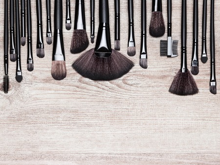 eyebrow trimming: Set of various natural bristle makeup brushes: for applying foundation, powder, blush, eyeshadow, eyebrow brushes and others. Professional tools of make-up artist on shabby wooden surface. Copy space Stock Photo