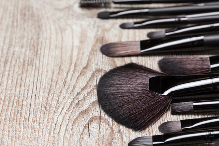 eyebrow trimming: Set of various natural bristle makeup brushes. Professional tools of make-up artist on shabby wooden surface. Copy space. Side view, shallow depth of field
