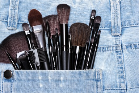eyebrow trimming: Professional tools of make-up artist in shabby jeans pocket. Sponge tip applicators and various makeup brushes: for applying foundation, powder, blush, eyeshadow, eyebrow brushes and others