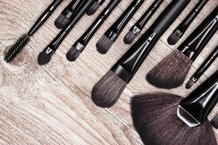 eyebrow trimming: Set of various natural bristle makeup brushes: for applying foundation, blush, eyeshadow, fan brush and others. Professional tools of make-up artist on shabby wooden surface Stock Photo