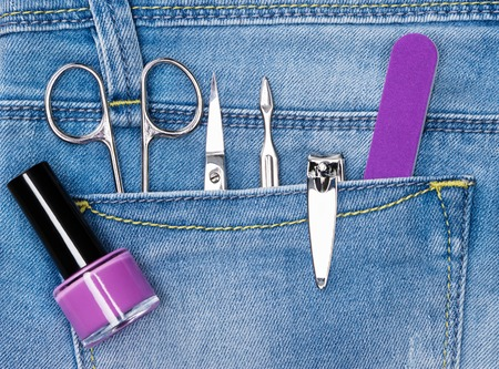 cuticle: Basic set of manicure tools in jeans pocket. Nail and cuticle scissors, cuticle trimmer, nail clippers, nailfile, nail polish