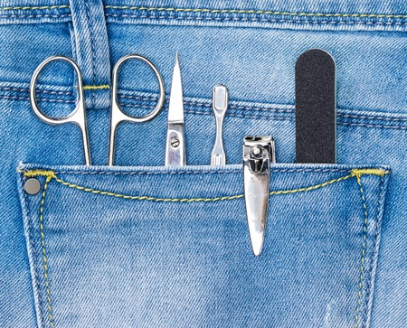 cuticle: Basic set of manicure tools in jeans pocket. Nail and cuticle scissors, cuticle trimmer, nail clippers, nailfile Stock Photo