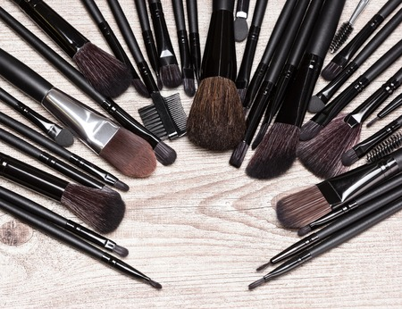 eyebrow trimming: Various makeup brushes arranged in semicircle on shabby wooden surface. Professional tools of make-up artist. Round frame with small copy space in the center Stock Photo