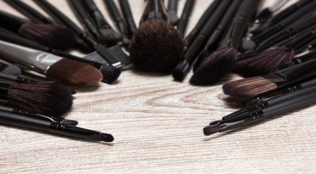 eyebrow trimming: Various makeup brushes arranged in semicircle on shabby wooden surface. Professional tools of make-up artist. Round frame with small copy space in the center. Shallow depth of field