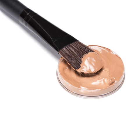 flaws: Close-up of makeup brush with liquid foundation on white background