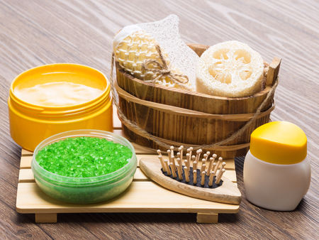 busting: Spa and pampering products and accessories. Green coarse sea salt, massager, wooden basket with loofah, body scrubber and pumice, natural body scrub, skin care cream on wooden surface