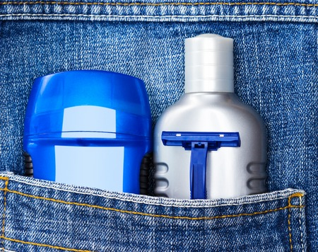 aftershave: Mens cosmetics. Antiperspirant deodorant, aftershave lotion and disposable razor in jeans pocket. Basic skin care cosmetic products and accessories for men. Toiletry and cosmetic travel kit Stock Photo