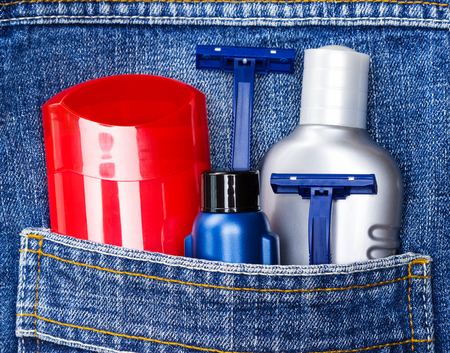 man health: Antiperspirant deodorant, shaving cream, aftershave lotion and disposable razors in jeans pocket. Basic skin care cosmetic products and accessories for men. Toiletry and cosmetic travel kit