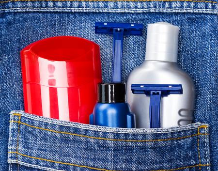 uomo rosso: deodorante antitraspirante, crema da barba, dopobarba e rasoi usa e getta in tasca dei jeans. Di base di cura della pelle prodotti cosmetici e accessori per uomo. Toilette e kit da viaggio cosmetici Archivio Fotografico