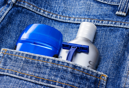 basic care: Mens cosmetics. Antiperspirant deodorant, aftershave lotion and disposable razor in jeans pocket. Basic skin care cosmetic products and accessories for men. Toiletry and cosmetic travel kit Stock Photo
