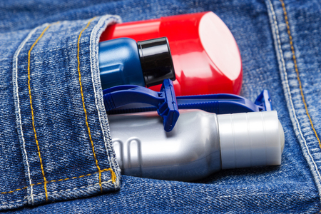 aftershave: Antiperspirant deodorant, shaving cream, aftershave lotion and disposable razors in jeans pocket. Basic skin care cosmetic products and accessories for men. Toiletry and cosmetic travel kit