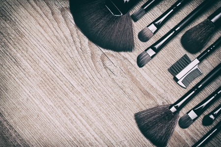 eyebrow trimming: Set of various makeup brushes: for applying powder, eyeshadow, eyebrow brushes, fan brushes and others. Professional tools of makeup artist on shabby wooden surface. Copy space. Retro style processing