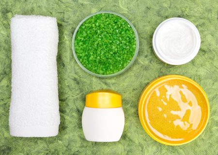 pampering: Spa and pampering products. Close-up of white towel, open jars filled with coarse sea salt, natural body scrub and skin care cream on green textured surface. Safe organic cosmetics