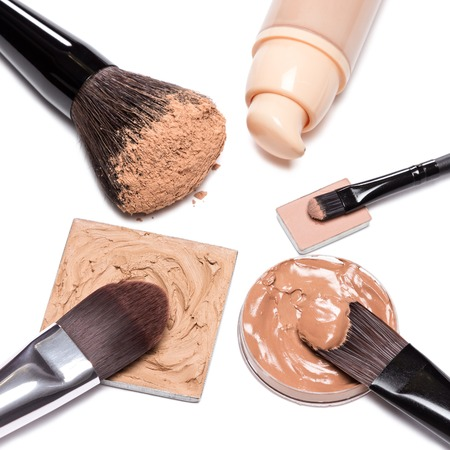 loose skin: Basic makeup products to create beautiful skin tone and complexion. Corrector, foundation, powder with brushes on white background Stock Photo