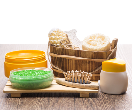 pampering: Spa and pampering products and accessories. Green sea salt, massager, wooden basket with loofah, body scrubber and pumice, natural body scrub, skin care cream on wooden surface. Copy space on top Stock Photo
