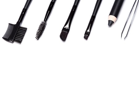 Accessories for care of the brows: brow comb / brush combo, spooly brush, angle brushes, eyebrow pencil, tweezers laid out in a row on white background. Eyebrow grooming tools. Copy space