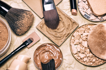 Makeup products to even skin tone and complexion on aged paper. Corrector, loose and compact powders, concealer pencil, liquid foundation with brushes and cosmetic sponges. Retro style processing Stock Photo