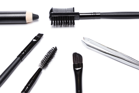 Accessories for care of the brows. Spooly brush, angle brushes, tweezers, brow comb / brush combo, black eyebrow pencil on white background. Eyebrow grooming tools
