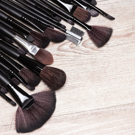 eyebrow trimming: Set of various makeup brushes: for applying foundation, powder, blush, eyeshadow, eyebrow brushes, fan brush and others. Professional tools of make-up artist on shabby wooden surface. Copy space