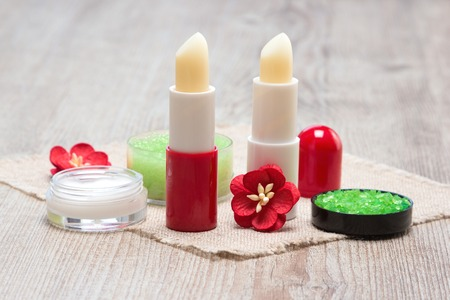 Cosmetics for lip skin care: sea salt, natural honey scrub with essential oils, lip cream and balms with flowers on shabby wooden surface and sackcloth napkin Фото со стока