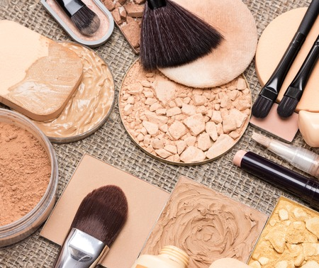 complexion: Basic makeup products to create beautiful skin tone and complexion. Correctors, foundation, powder, bronzer with brushes and cosmetic sponges on sackcloth Stock Photo
