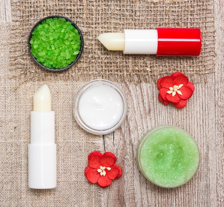 Cosmetics for lip skin care: close-up of coarse sea salt, natural honey scrub with essential oils, moisturizing lip cream and balms with flowers on shabby wooden surface and sackcloth napkins 스톡 콘텐츠