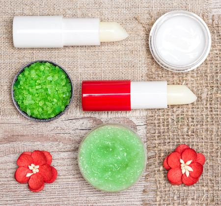 Cosmetics for lip skin care: close-up of coarse sea salt, natural honey scrub with essential oils, moisturizing lip cream and balms with flowers on shabby wooden surface and sackcloth napkins Banque d'images