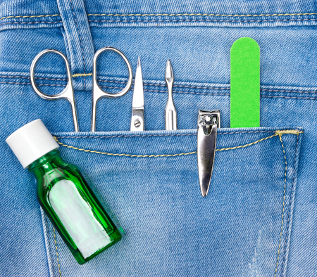cuticle pusher: Basic set of manicure tools in blue jeans pocket. Nail and cuticle scissors, cuticle trimmer, nail clippers, nailfile, nail strengthener
