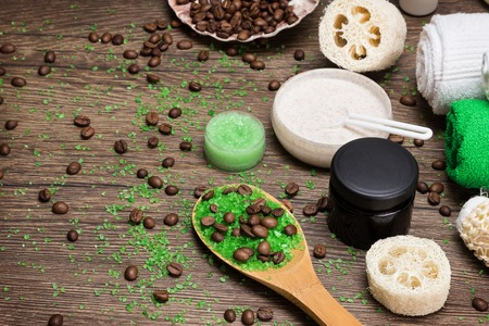 busting: Anti-cellulite cosmetics with caffeine. Wooden spoon with green sea salt and coffee beans, natural body scrubs, skin care cream, body scrubbers, towels. Spa and cellulite busting products. Copy space Stock Photo