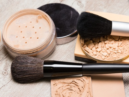 loose skin: Different types of makeup cosmetic products to even out skin tone and complexion with brushes on shabby wooden surface. Cream-to-powder foundation, compact powder, jar of loose powder Stock Photo