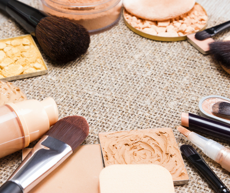 even: Makeup products to even out skin tone and create the perfect complexion laid out as frame on sackcloth. Foundation, concealers, various types of powder. Side view, shallow depth of field. Copy space Stock Photo