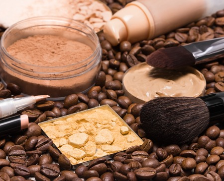 loose skin: Basic makeup products to create beautiful skin tone and complexion. Concealers, liquid foundation, compact, loose and shimmer golden powder with brushes on coffee beans. Focus on the front brush