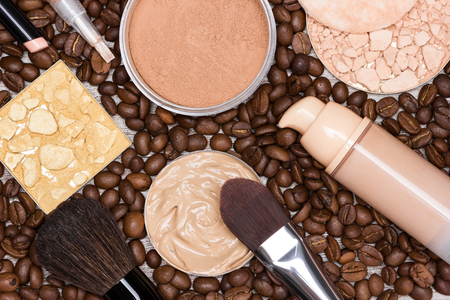 loose skin: Basic makeup products to create beautiful skin tone and complexion. Concealers, liquid foundation, compact, loose and shimmer golden powder with brushes on coffee beans