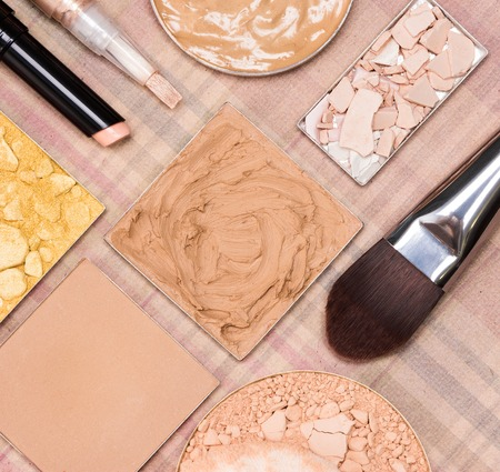 complexion: Basic makeup products to create beautiful skin tone and complexion. Correctors, foundation, powder with flat brush and cosmetic sponge on plaid background