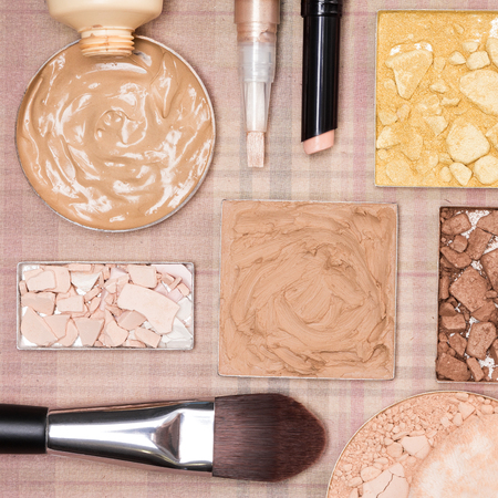 flaws: Cream-to-powder and liquid foundation, correctors, shimmer powder golden color, crushed compact powder, bronzer with flat makeup brush and cosmetic sponge on plaid background Stock Photo