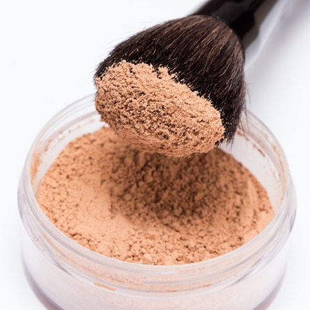 Close-up of makeup brush with loose cosmetic powder on light background. Shallow depth of field, focus on powdery brush tip Standard-Bild