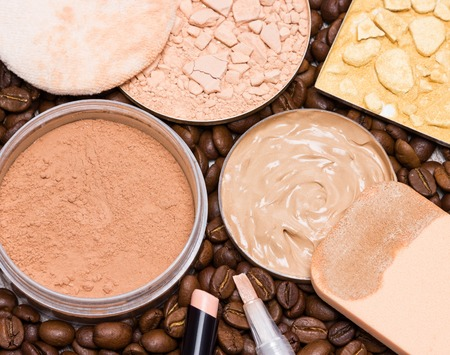 loose skin: Concealers, liquid foundation, open jar of loose cosmetic powder, crushed compact and shimmer powder golden color on coffee beans. Makeup products to create the perfect skin tone and complexion Stock Photo