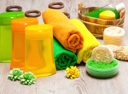 scrubbers: Shower gel, towels, sea salt, body scrubbers and other spa cosmetics and accessories on shabby wooden surface. Bright bathing products for excellent summer mood Stock Photo
